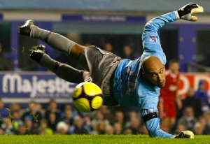 Everton's Howard dives for the ball during their FA Cup fourth round replay soccer match against Liverpool in Liverpool
