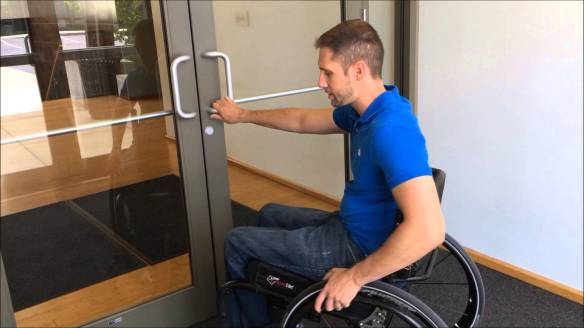 Man in wheelchair about to open a door